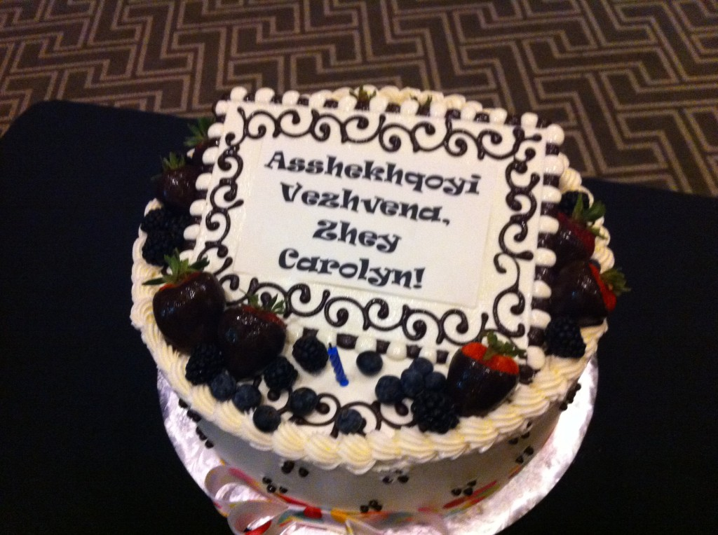 "A cake with ""Asshekhqoyi vezhvena, zhey Carolyn!"" written on it."